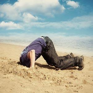 مردی در ساحل دریا سر خود را در شن فرو برده است